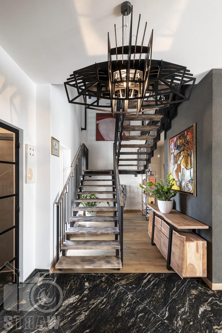 Zdjęcia domu na sprzedaż w lokalizacji Warszawa Wilanów, żyrandol i schody na piętro.