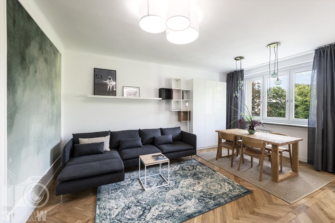 Sesja fotograficzna nieruchomości na wynajem, salon, sofa i dywan, stolik kawowy i stół drewniany z krzesłami.