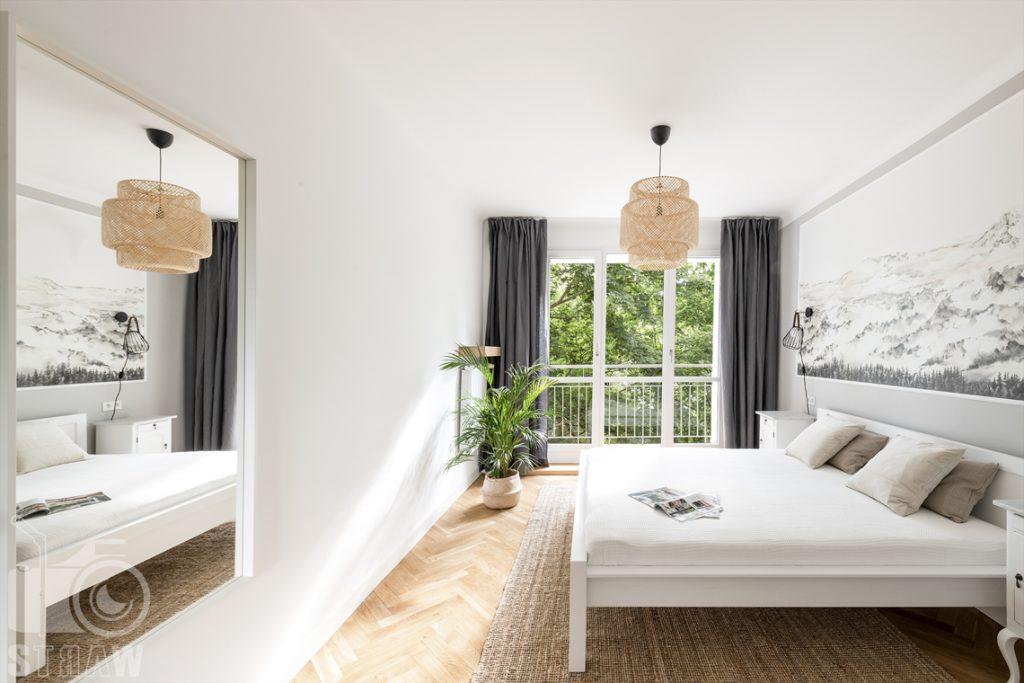 Sesja fotograficzna nieruchomości na wynajem, sypialnia z dużym lustrem i palmą w donicy .