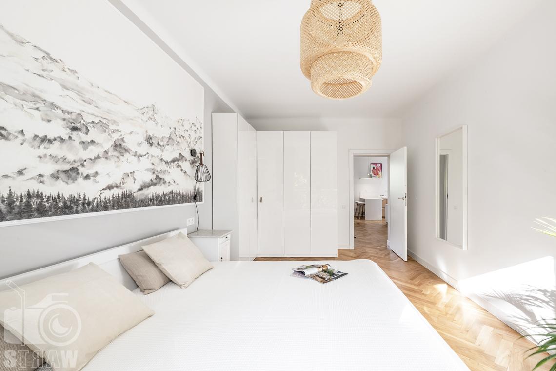 Sesja fotograficzna nieruchomości na wynajem, sypialnia, łóżko widok na salon i jadalnię.