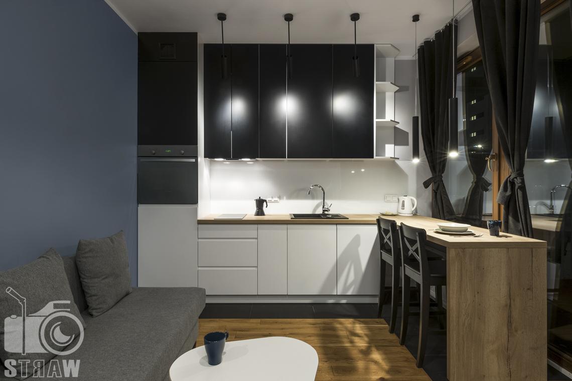 Zdjęcia apartamentu na wynajem krótko lub długoterminowy, fotografia wnętrz Warszawa, aneks kuchenny, jadalnia, wyspa, krzesła, zlewozmywak, kanapa, stolik kawowy.