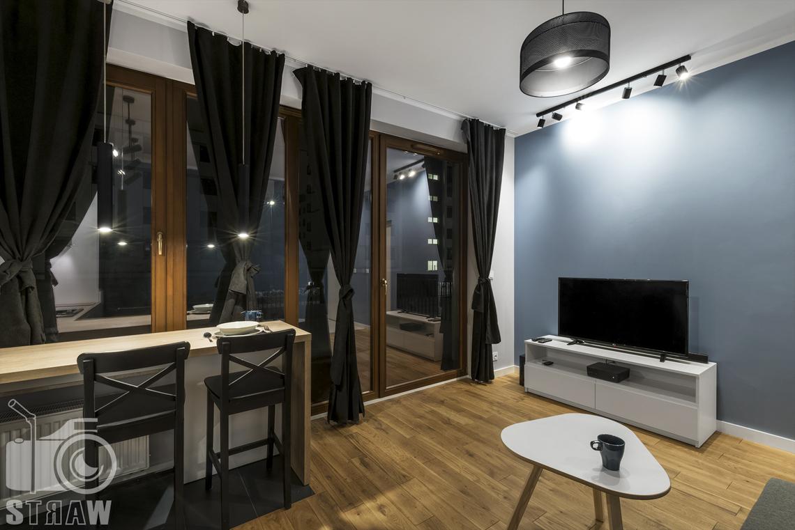 Zdjęcia apartamentu na wynajem krótko lub długoterminowy, fotografia wnętrz Warszawa, jadalnia, wyspa, krzesła, okna na calej ścianie, telewizor, szafka RTV, stolik kawowy.