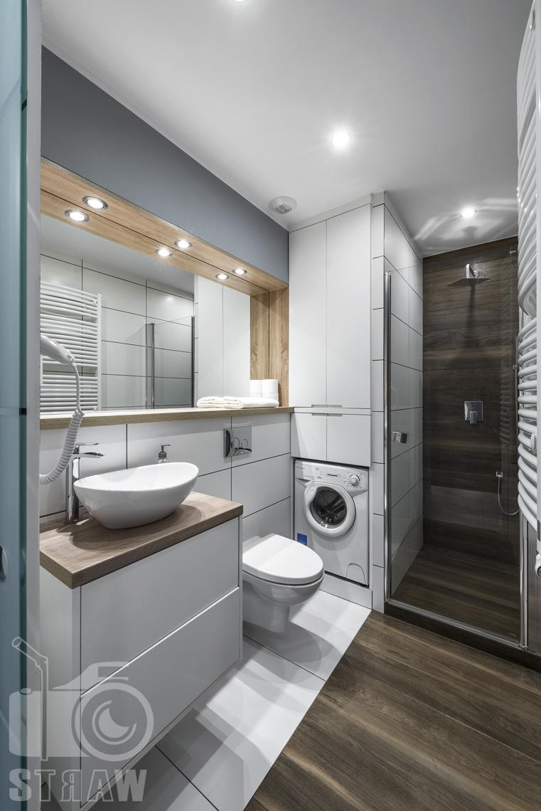 Zdjęcia apartamentów na wynajem, fotografia wnętrz Warszawa, łazienka, szafka łazienkowa z umywalką w formie misy, wc, lustra, pralka, szafki, kabina prysznicowa.