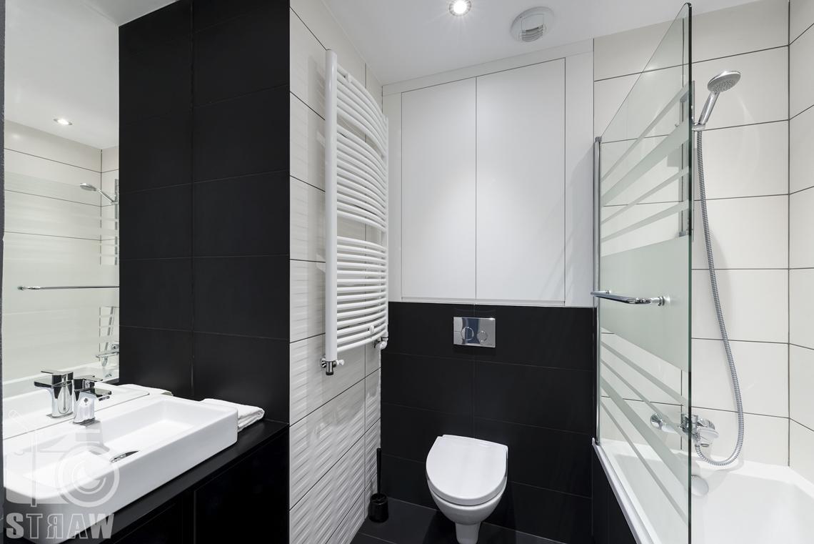 Zdjęcia apartamentu na wynajem krótko lub długoterminowy, fotografia wnętrz Warszawa, łazienka, umywalka, wc, prysznic, wanna, zasłona szklana.