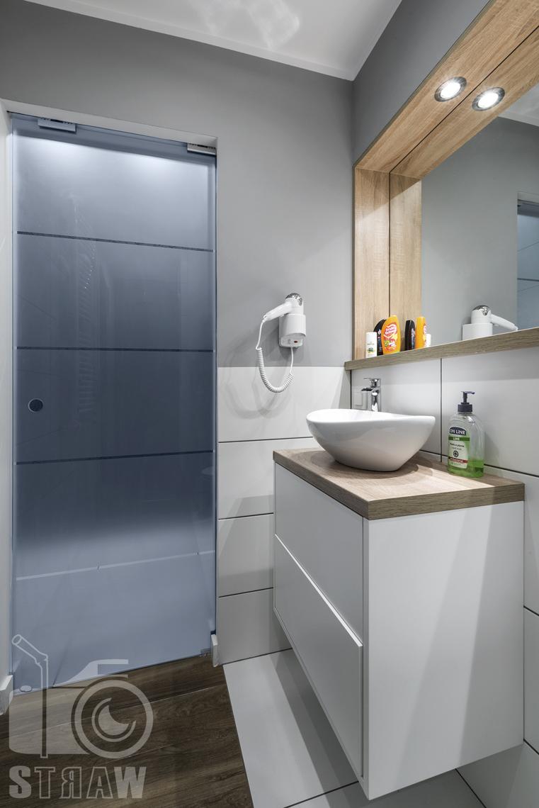 Zdjęcia apartamentów na wynajem, fotografia wnętrz Warszawa, łazienka, szafka łazienkowa z umywalką, suszarka, lustro.