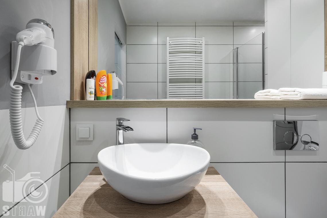 Zdjęcia apartamentów na wynajem, fotografia wnętrz Warszawa, łazienka, umywalka, suszarka, lustro, ręczniki, kosmetyki.