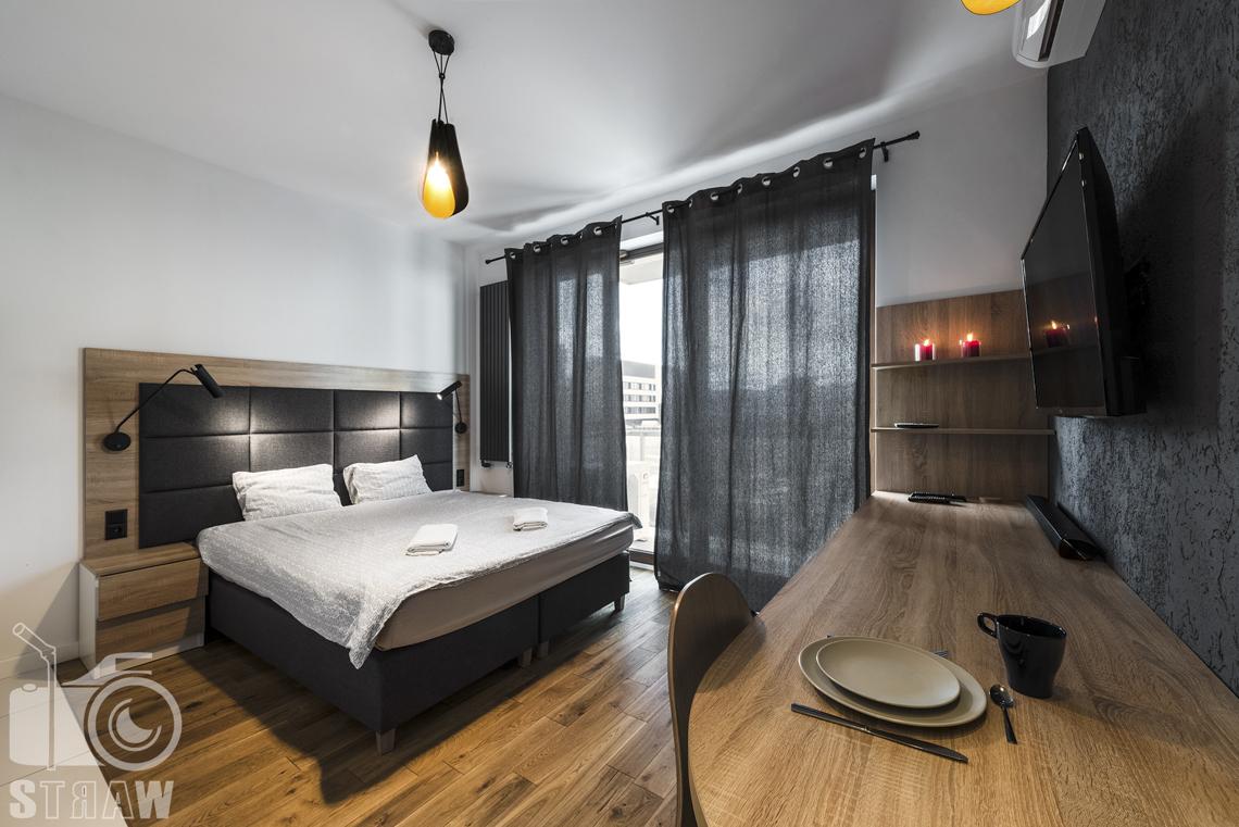 Zdjęcia apartamentów na wynajem, fotografia wnętrz Warszawa, sypialnia, jadalnia, telewizor, łóżko dwuosobowe, stół długi, dwie półki, okno duże z ciemnymi zasłonami.