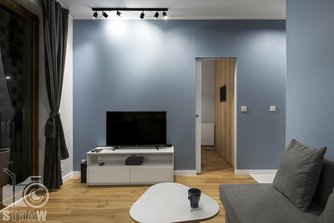 Zdjęcia apartamentu na wynajem krótko lub długoterminowy, fotografia wnętrz Warszawa, salon, telewizor na szafce RTV, kanapa z poduchą, stolik kawowy, drzwi do sypialni.