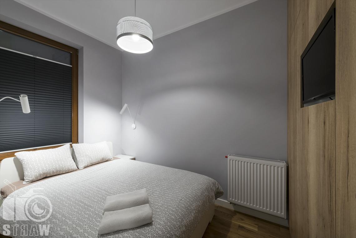 Zdjęcia apartamentu na wynajem krótko lub długoterminowy, fotografia wnętrz Warszawa, sypialnia, łóżko dwuosobowe, okno, telewizor, lampa wisząca, lampki nocne.