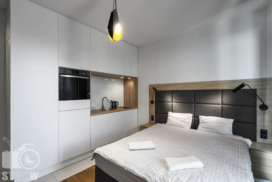 Zdjęcia apartamentów na wynajem, fotografia wnętrz Warszawa, sypialnia z aneksem kuchennym, lóżko dwuosobowe, lampki nocne, szafki nocne.