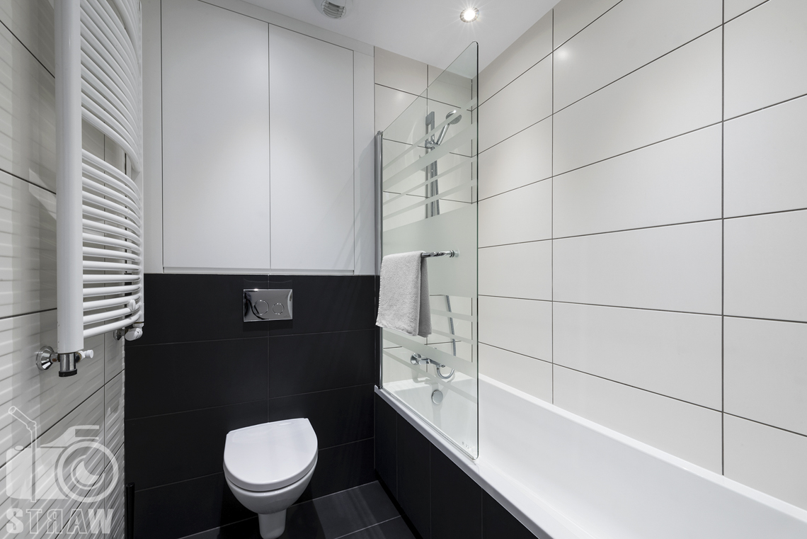 Zdjęcia apartamentu na wynajem krótko lub długoterminowy, fotografia wnętrz Warszawa, toaleta, wc, szafka, kaloryfer, wanna.