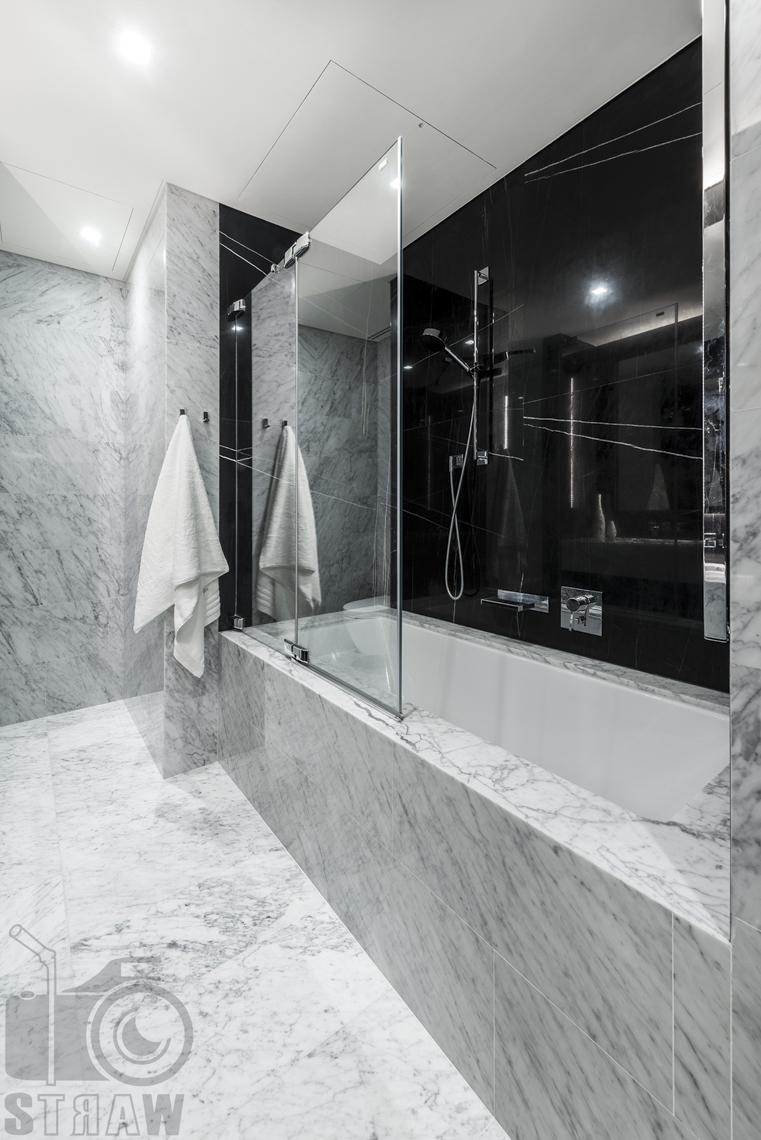 Fotografia wnętrz na wynajem długoterminowy, zdjęcia nieruchomości Warszawa, łazienka, wanna, zasłona szklana przy prysznicu, ręcznik.