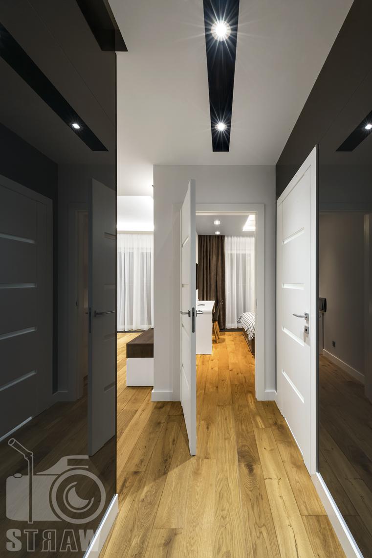 Zdjęcia apartamentów na wynajem krótkoterminowy, fotografia wnętrz Warszawa, hol, drzwi wejściowe, w tle salon, sypialnia.