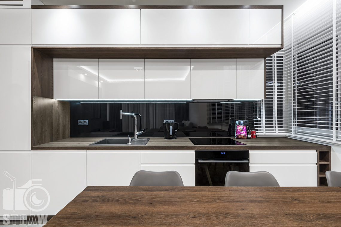Zdjęcia apartamentów na wynajem krótkoterminowy, fotografia wnętrz Warszawa, aneks kuchenny, szafki kuchenne, zlewozmywak, płyta grzewcza, piecyk, jadalnia, wyspa, krzesła, okna z żaluzjami.