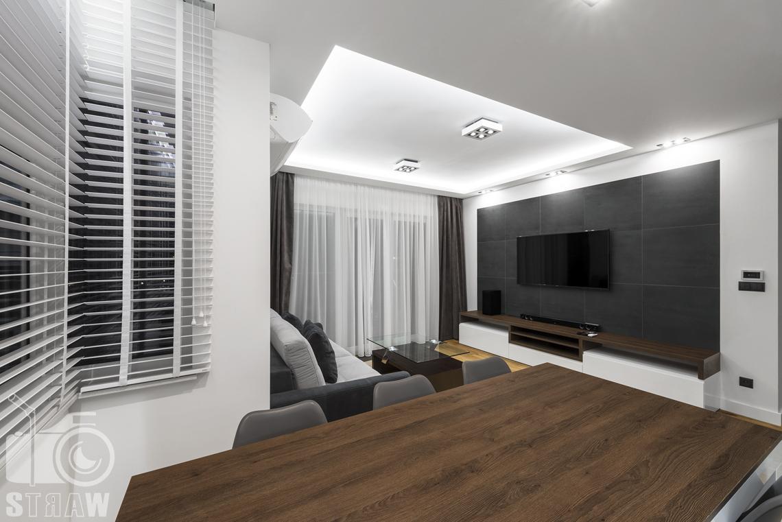 Zdjęcia apartamentów na wynajem krótkoterminowy, fotografia wnętrz Warszawa,jadalnia, wyspa, krzesła, salon, telewizor, półka, kanapa, stolik kawowy.
