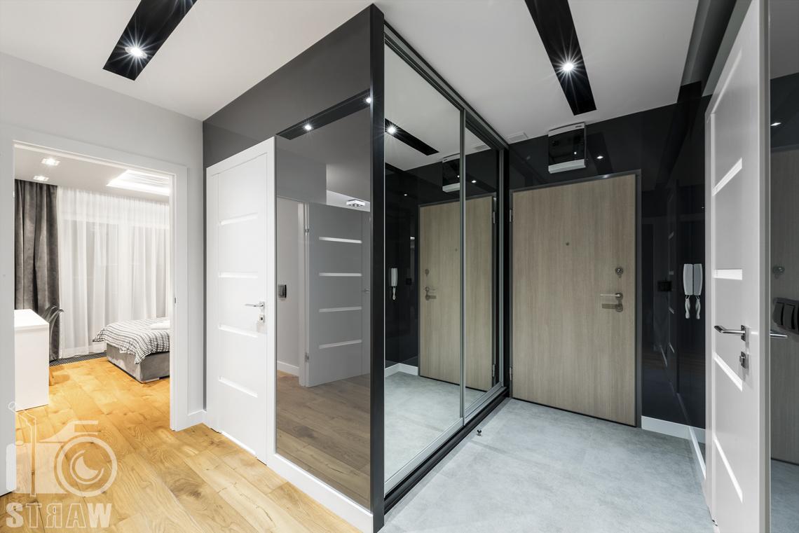 Zdjęcia apartamentów na wynajem krótkoterminowy, fotografia wnętrz Warszawa,przedpokój, drzwi wejściowe, szafa na ubrania z lustrami, widok na sypialnię.