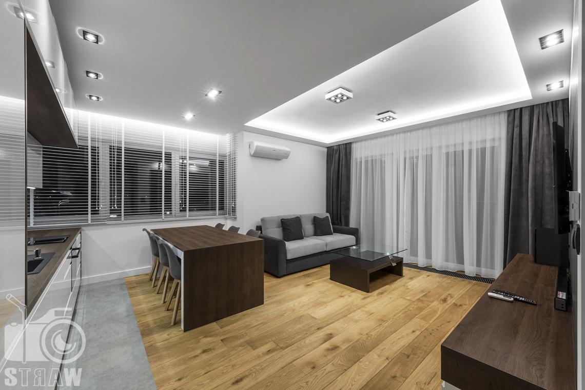 Zdjęcia apartamentów na wynajem krótkoterminowy, fotografia wnętrz Warszawa,salon, z aneksem kuchennym, jadalnia, wyspa, kanapa, stolik kawowy, okno na całą ścianę z firanami i zasłonami.
