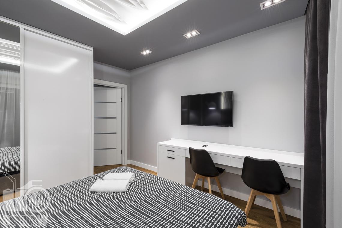 Zdjęcia apartamentów na wynajem krótkoterminowy, fotografia wnętrz Warszawa, sypialnia, łóżko dwuosobowe, telewizor, biurko, dwa krzesła, szafa z lustrem.