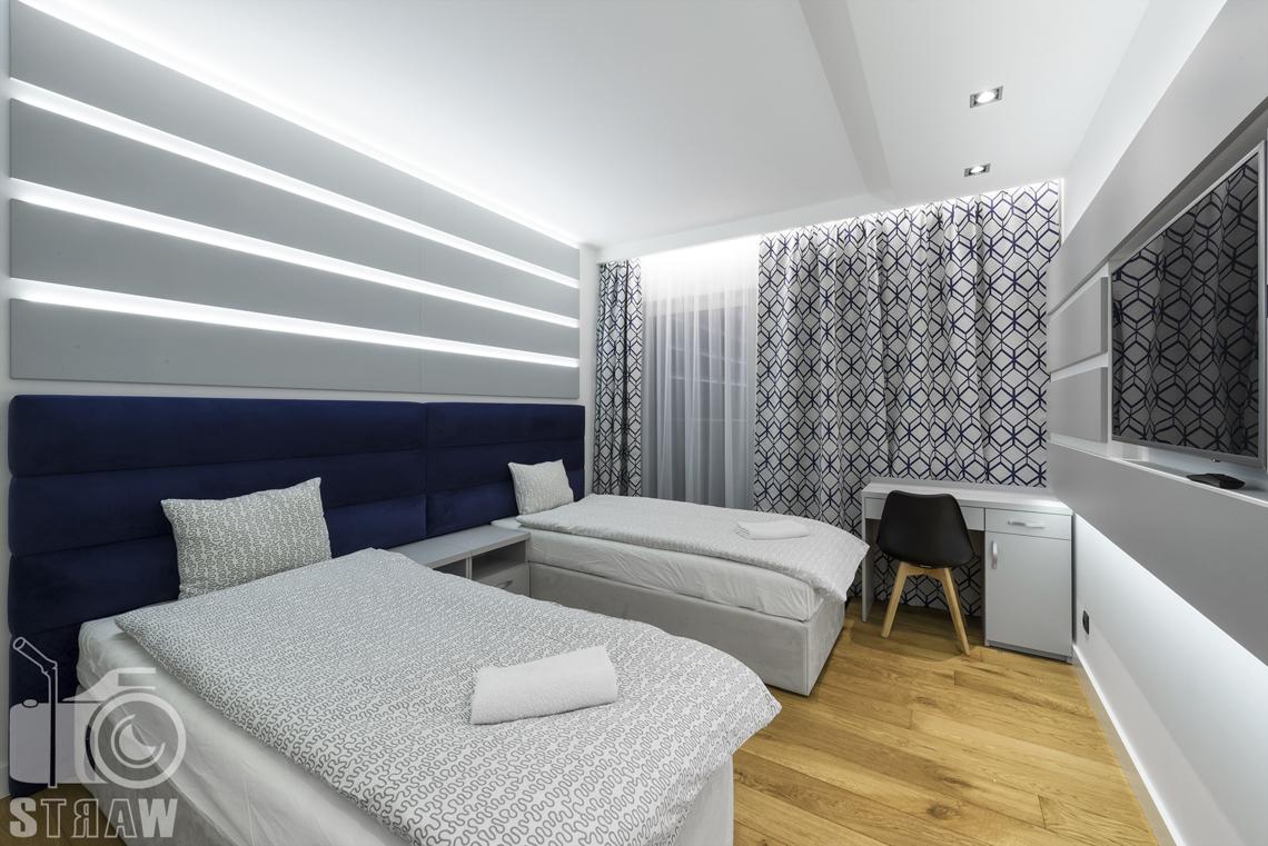 Zdjęcia apartamentów na wynajem krótkoterminowy, fotografia wnętrz Warszawa, sypialnia dla dwóch osób, dwa łóżka pojedyncze, szafka nocna, telewizor, biurko.