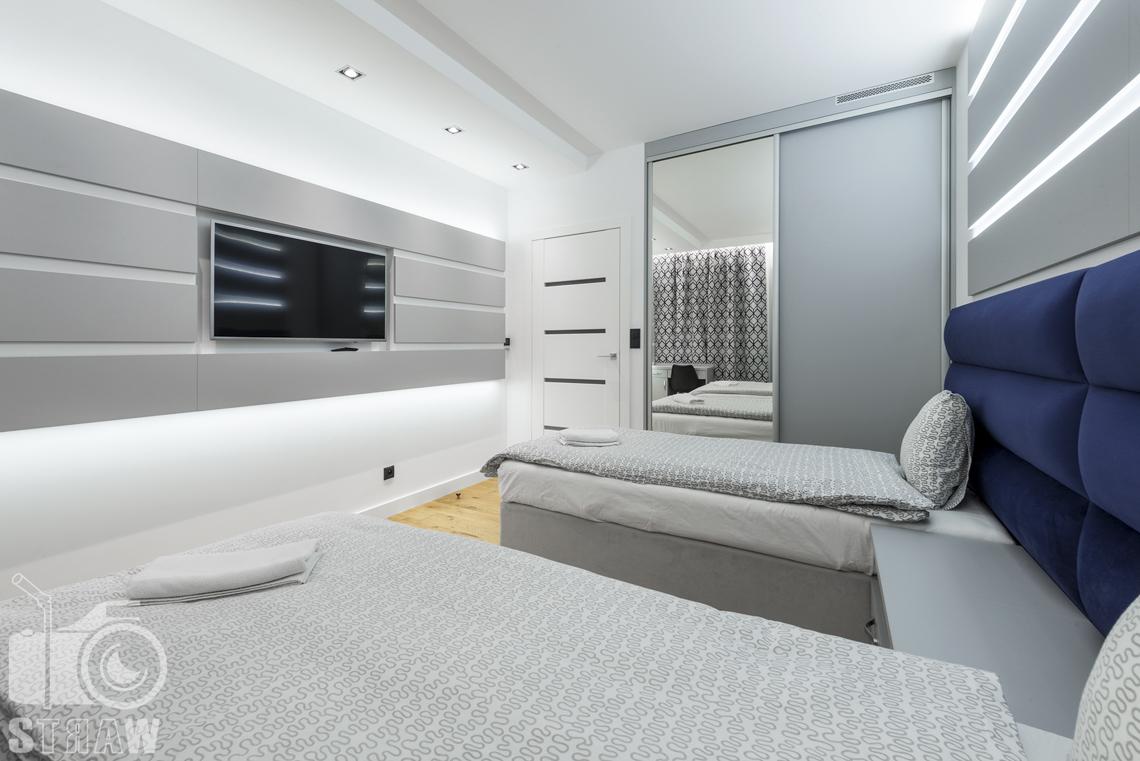 Zdjęcia apartamentów na wynajem krótkoterminowy, fotografia wnętrz Warszawa, sypialnia dla dwóch osób, dwa łóżka pojedyncze, telewizor, szafa z lustrem, drzwi wejściowe.