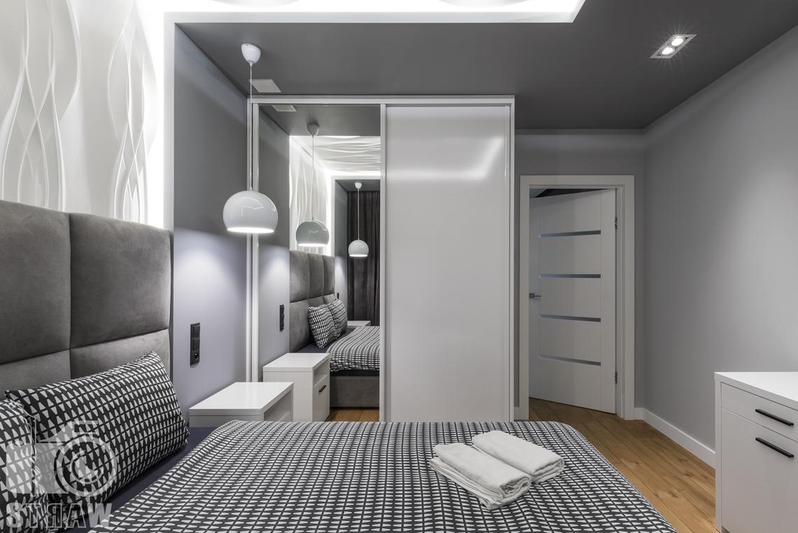 Zdjęcia apartamentów na wynajem krótkoterminowy, fotografia wnętrz Warszawa, sypialnia z łóżkiem dwuosobowym, szafa z lustrem, szafka nocna, lampa nocna wisząca, drzwi wejściowe.