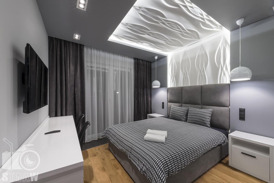 Zdjęcia apartamentów na wynajem krótkoterminowy, fotografia wnętrz Warszawa, sypialnia dwuosobowa, łóżko dwuosobowe, stół na całej ścianie, dwa krzesła, telewizor, okno duże z firana i zasłonami, dwie szafki nocne