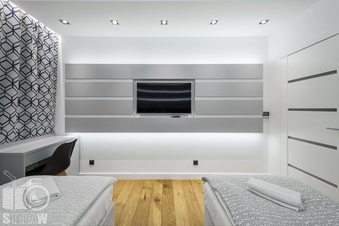 Zdjęcia apartamentów na wynajem krótkoterminowy, fotografia wnętrz Warszawa, sypialnia, dwa łóżka pojedyncze, biurko, krzesło, telewizor, okno zasłonięte, ręczniki.
