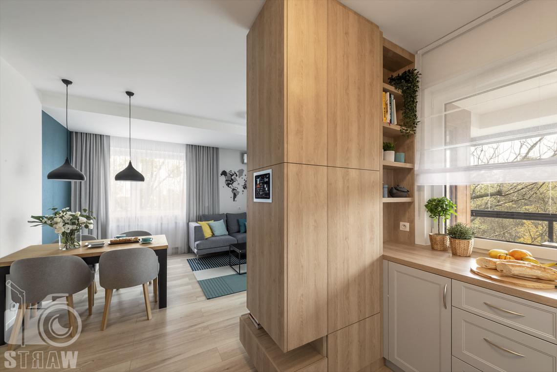 Sesje fotograficzne wnętrz dla projektantów i architektów wnętrz, kuchnia, szafki i szuflady pod oknem, salon, jadalnia, stół prostokatny z krzesłami, oświetlenie dwiema lampami wiszącymi.
