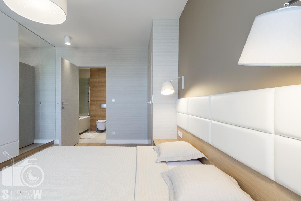 Zdjęcia wnętrz zrealizowanych projektów wystroju wnętrza, sesje fotograficzne dla projektantów, sypialnia, łóżko dwuosobowe, lampki nocne, szafa z lustrami, wyjście do łazienki.