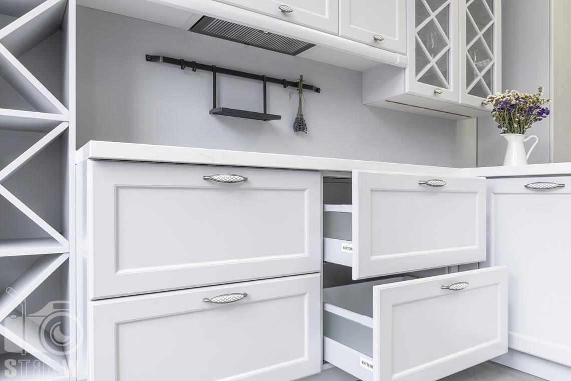 Fotografia wnętrz, zdjęcia showroom kittchen, zabudowa kuchenna biała, z otwartymi dwiema szufladami.