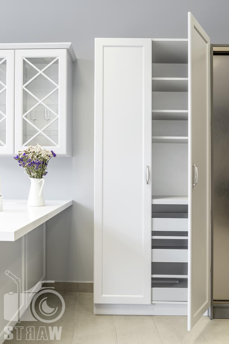 Fotografia wnętrz, zdjęcia showroom kittchen, szafa wolno stojąca biała z półkami i szufladami.