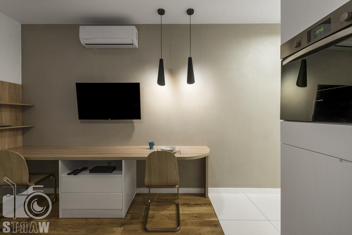 Fotografia wnętrz apartamentów na wynajem, krótko lub długoterminowy, zdjęcia wnętrz warszawa,jadalnia, stół, telewizor, lampy wiszące, półka, klimatyzator.