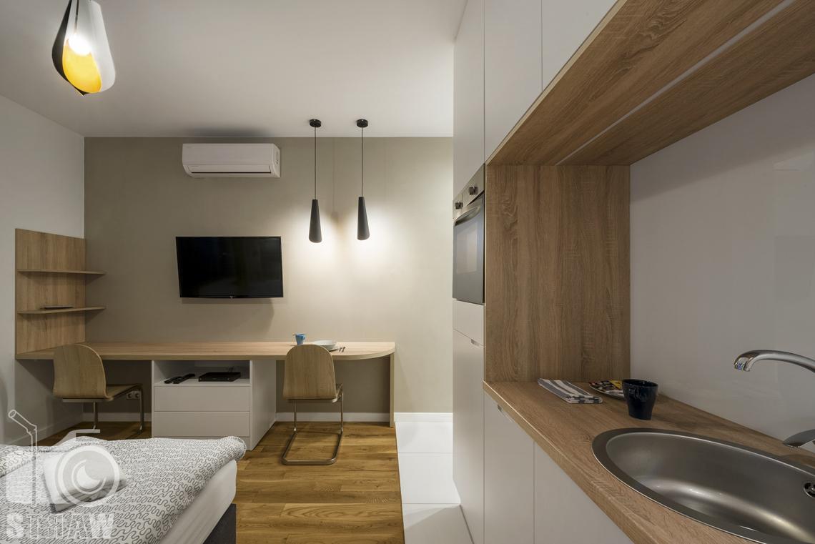 Fotografia wnętrz apartamentów na wynajem, krótko lub długoterminowy, zdjęcia wnętrz warszawa,aneks kuchenny, zlewozmywak, jadalnia, stół, krzesła, półka, telewizor.