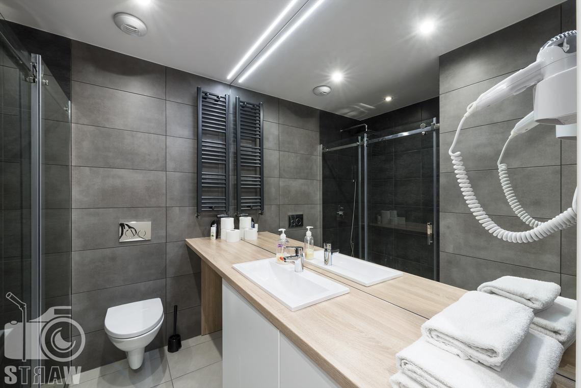 Fotografia wnętrz apartamentów na wynajem, krótko lub długoterminowy, zdjęcia wnętrz warszawa, łazienka, suszarka, ręczniki, wc, szafki łazienkowe, umywalka, lustro.