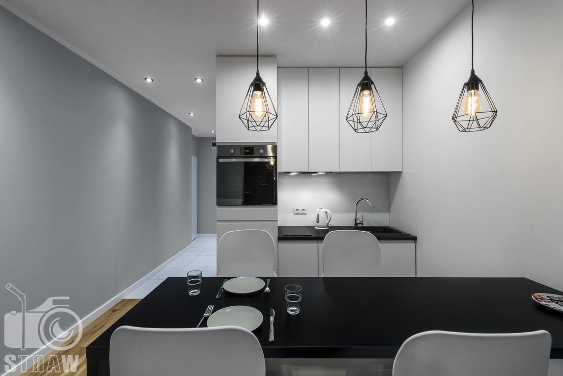 Fotografia apartamentów na wynajem, zdjęcia wnętrz Warszawa, jadalnia, aneks kuchenny, trzy lampy wiszące, wyspa z czarnym blatem, krzesła.