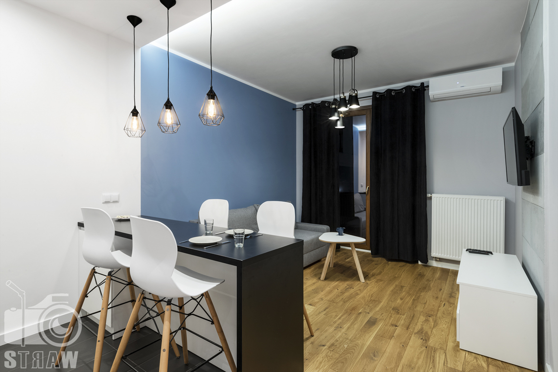 Fotografia apartamentów na wynajem, zdjęcia wnętrz Warszawa, jadalnia, wyspa, cztery krzesła, kanapa, stolik kawowy, okno z zasłonami, telewizor, szafka.