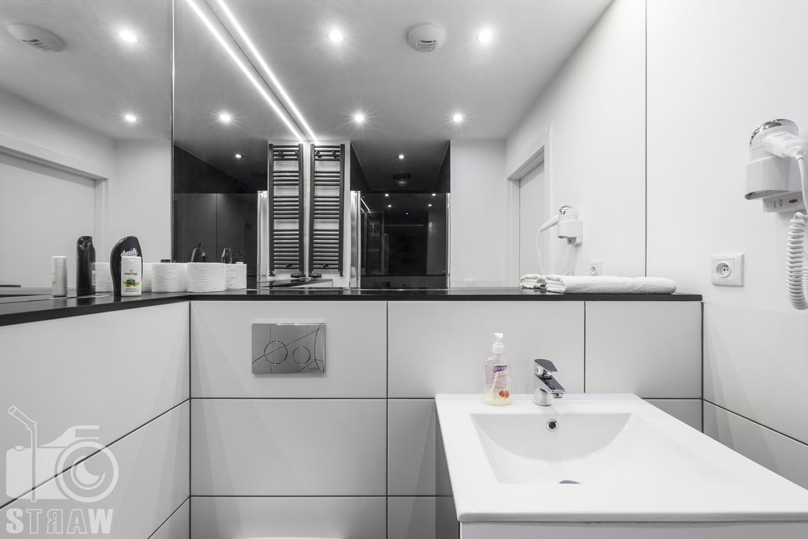 Fotografia apartamentów na wynajem, zdjęcia wnętrz Warszawa, łazienka, umywalka, suszarka, lustra.