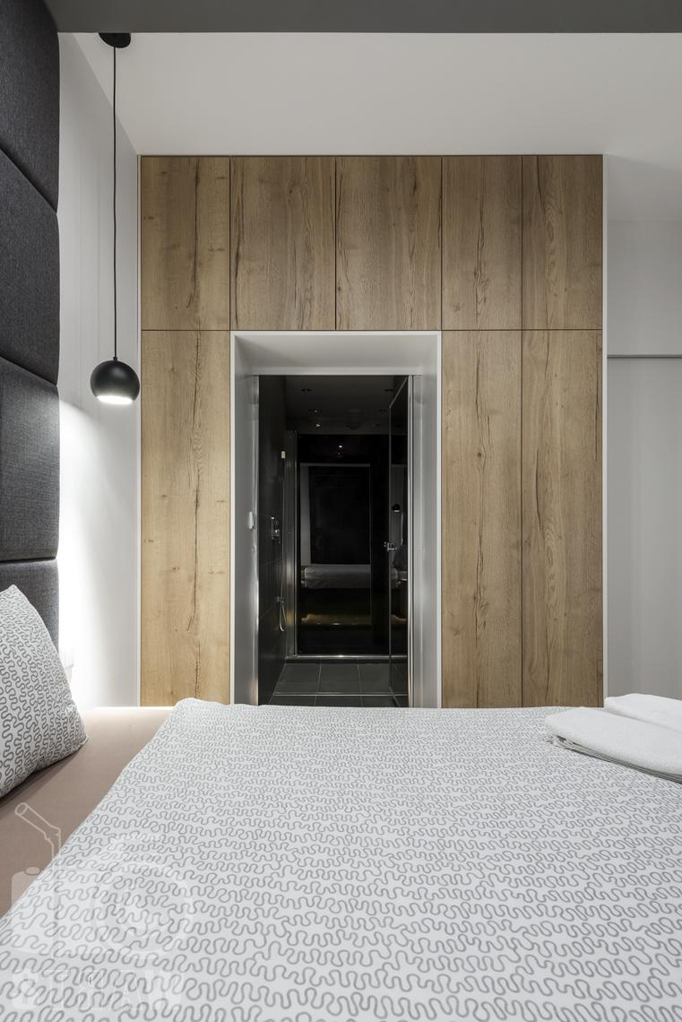 Fotografia apartamentów na wynajem, zdjęcia wnętrz Warszawa, sypialnia, łóżko dwuosobowe, drzwi do łazienki.