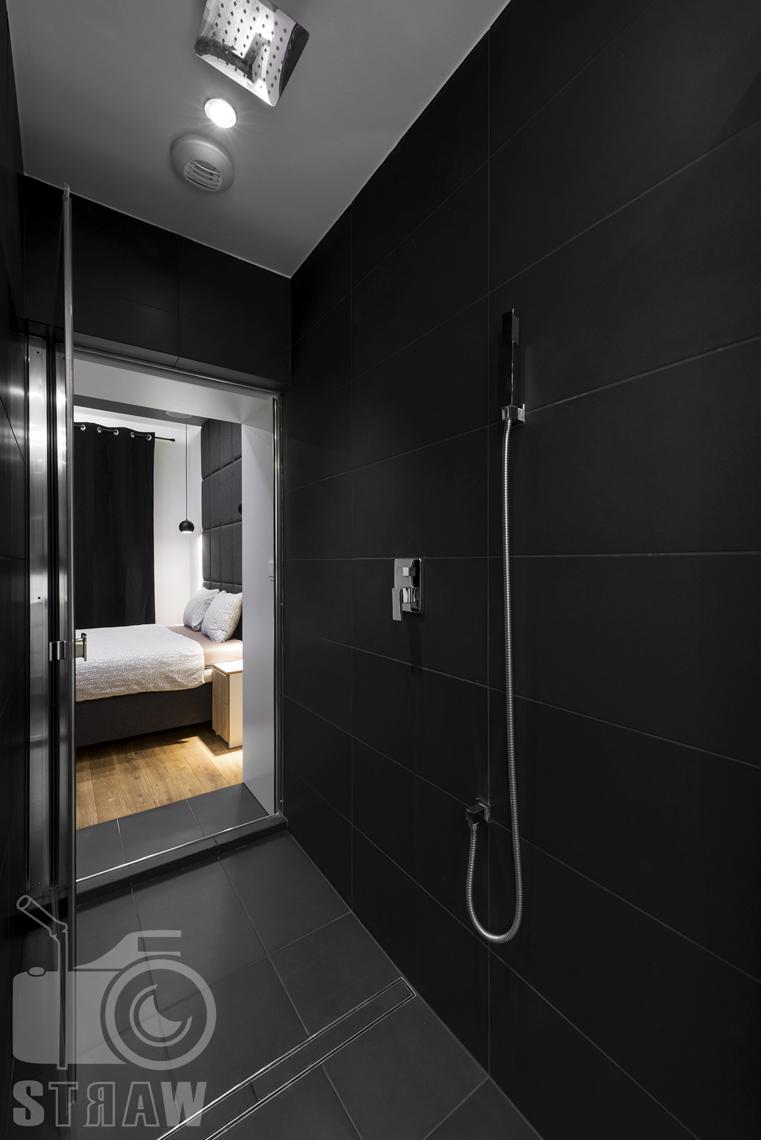 Fotografia apartamentów na wynajem, zdjęcia wnętrz Warszawa, łazienka, kabina prysznicowa z deszczownicą, w tle sypialnia.