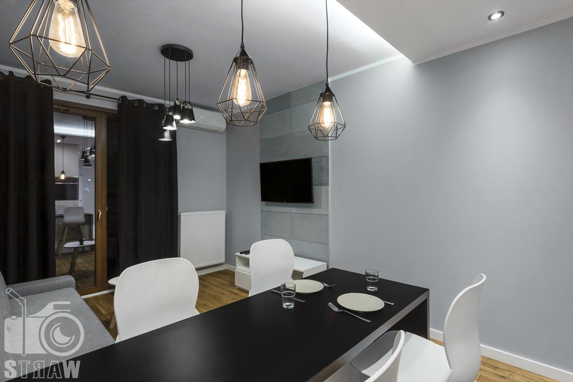 Fotografia apartamentów na wynajem, zdjęcia wnętrz Warszawa, jadalnia, wyspa, krzesła, w tle telewizor, okno balkonowe.