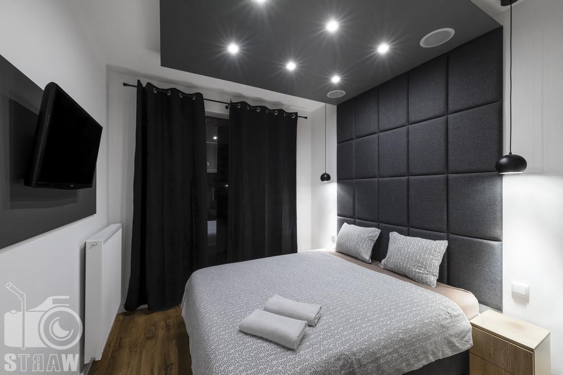 Fotografia apartamentów na wynajem, zdjęcia wnętrz Warszawa, sypialnia, łóżko dwuosobowe, szafka nocna, telewizor, kaloryfer, okno, zasłony czarne.