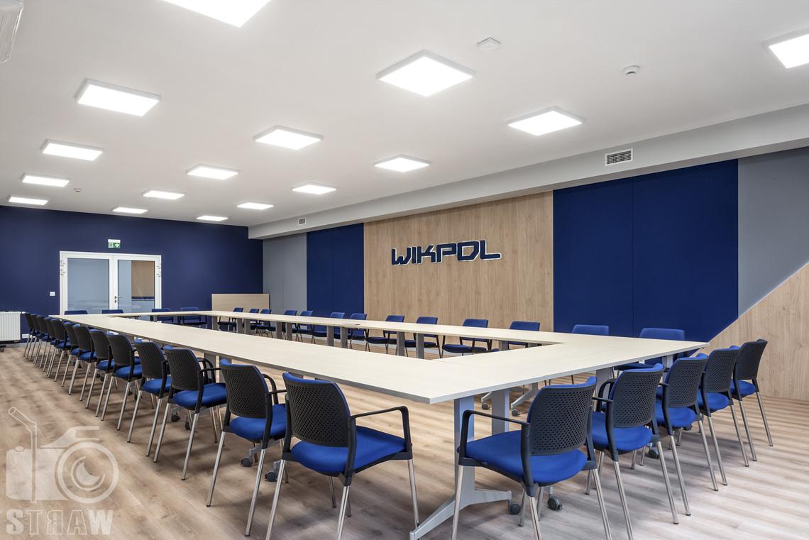 Sesje fotograficzne wnętrz biurowych, zdjęcia wnętrz komercyjnych, zdjęcia wnętrz w siedzibie firmy Wikpol, na zlecenie dystrybutora mebli firmy Logan, sala konferencyjna, logo firmy, stół duży, krzesła, drzwi wejściowe.