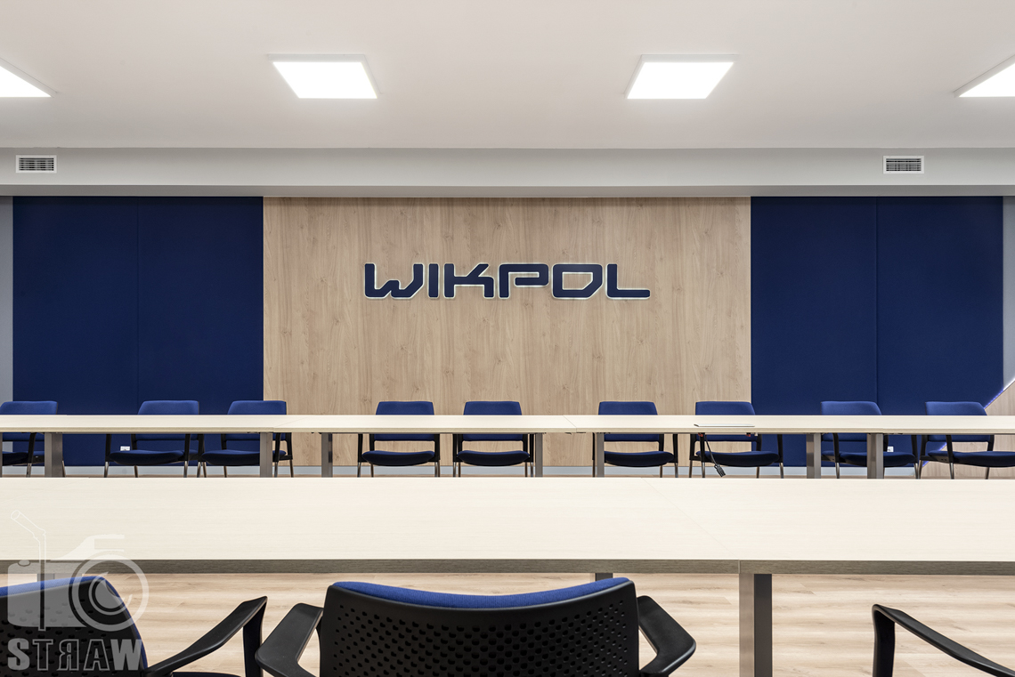 Sesje fotograficzne wnętrz biurowych, zdjęcia wnętrz komercyjnych, zdjęcia wnętrz w siedzibie firmy Wikpol, na zlecenie dystrybutora mebli firmy Logan, sala konferencyjna, nazwa firmy, stół długi, fotele dla uczestników narady.