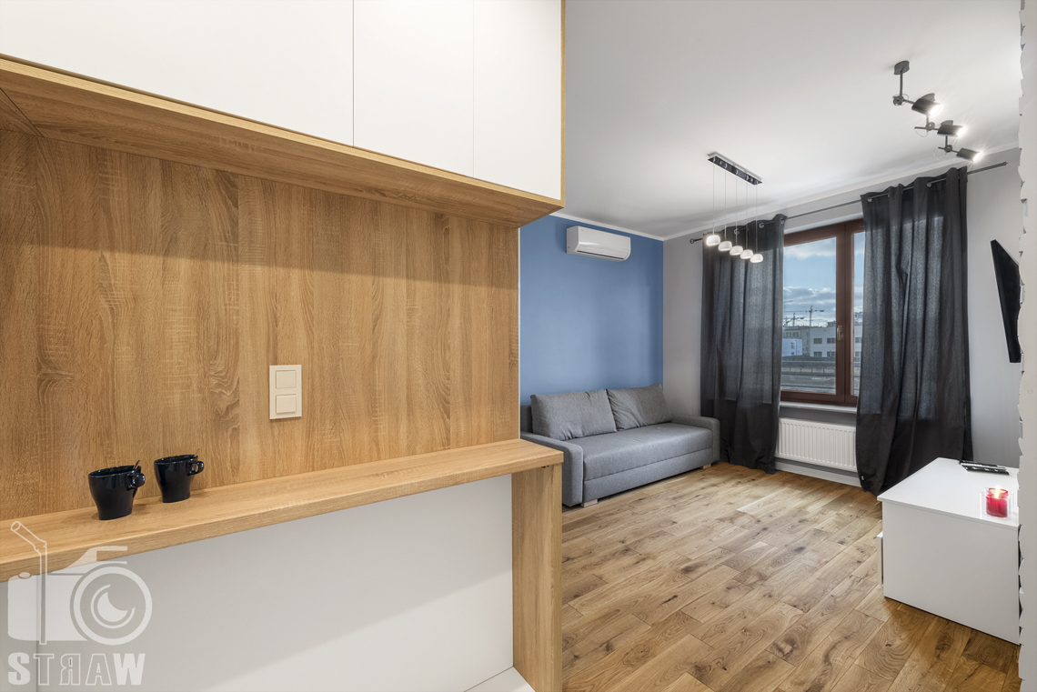 Sesje zdjęciowe apartamentów na wynajem, fotograf wnętrz Warszawa, z aneksu widac salon, kanapa, okno, klimatyzator, szafka.
