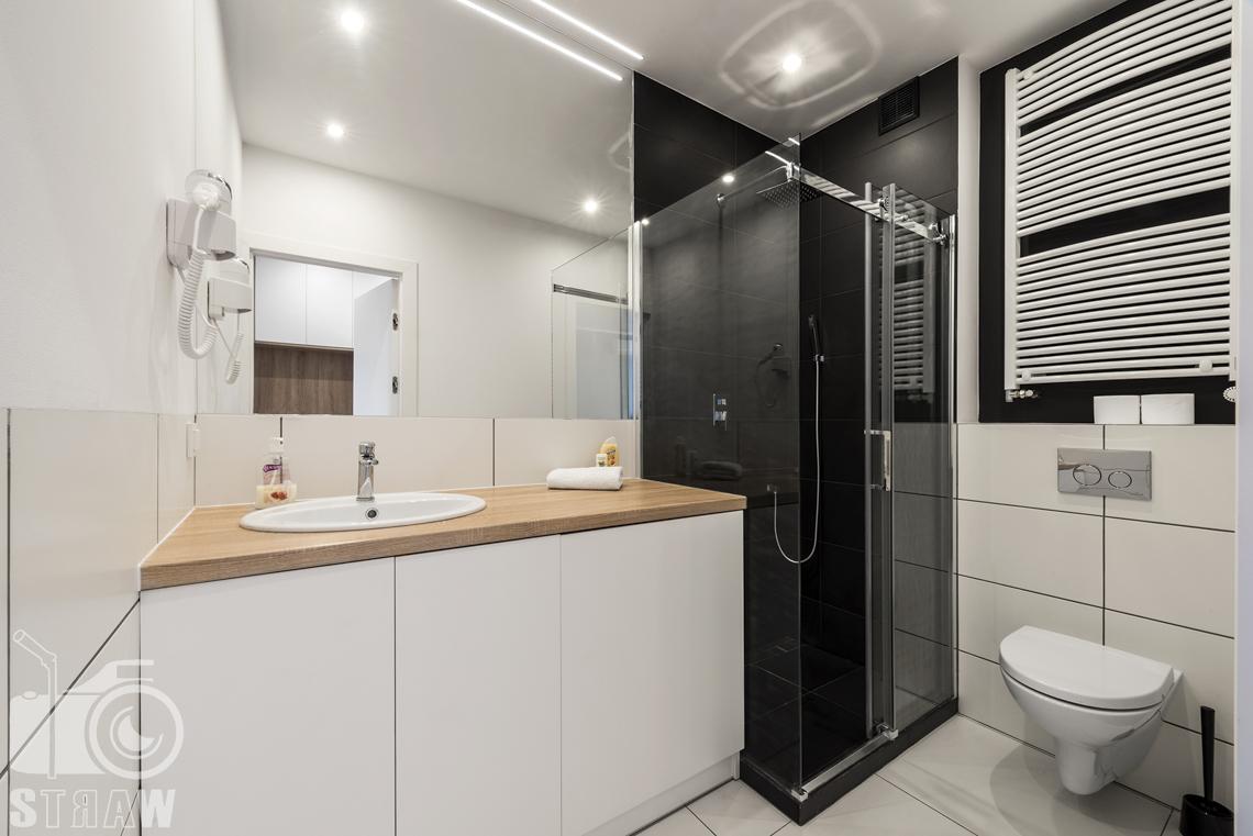 Sesje zdjęciowe apartamentów na wynajem, fotograf wnętrz Warszawa, łazienka, kabina prysznicowa, szafki łazienkowe, umywalka, lustra, wc, kaloryfer.