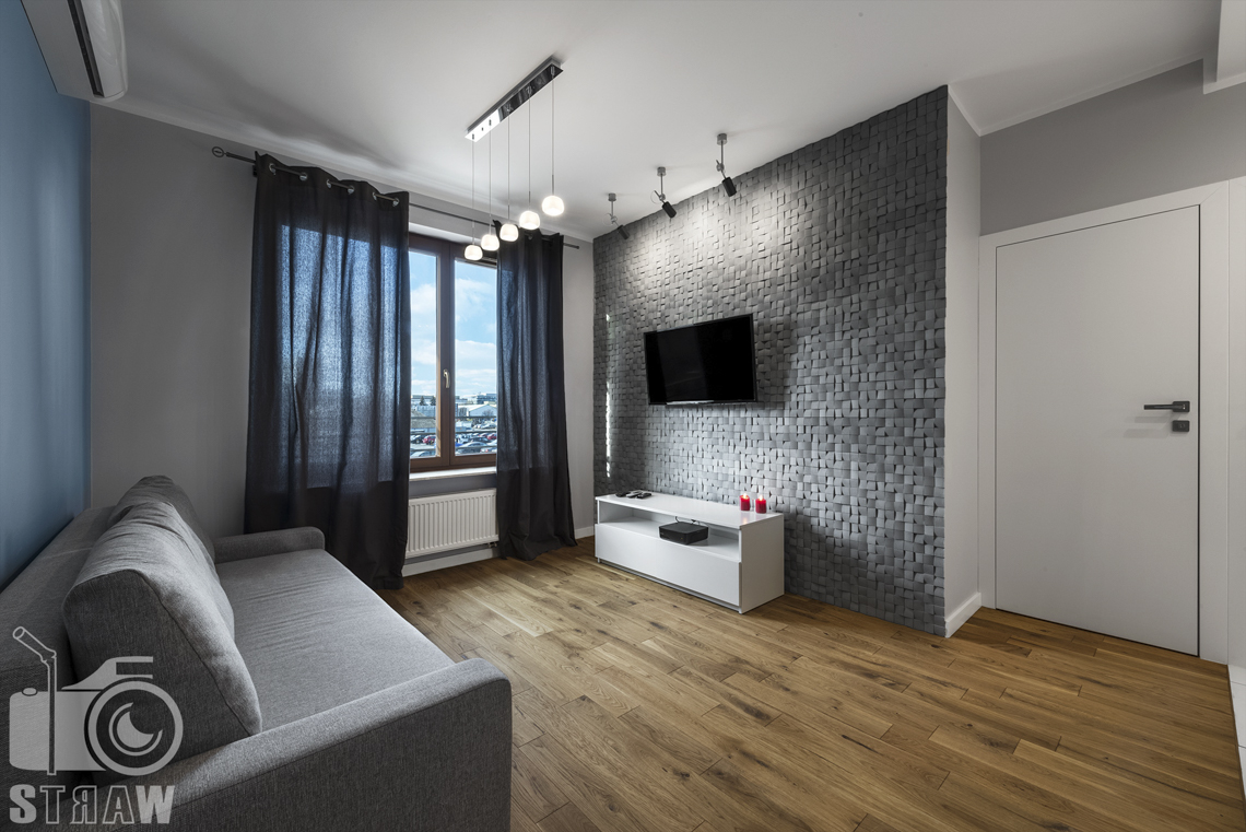 Sesje zdjęciowe apartamentów na wynajem, fotograf wnętrz Warszawa, salon, kanapa, telewizor, szafka rtv, okno z ciemnymi zasłonami, lampy wiszące i punktowe, drzwi wejściowe.