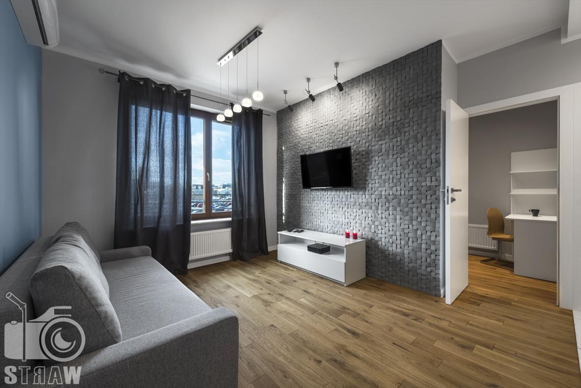 Sesje zdjęciowe apartamentów na wynajem, fotograf wnętrz Warszawa, salon, kanapa, telewizor, szafka biała, okno, drzwi prowadzą do gabinetu.