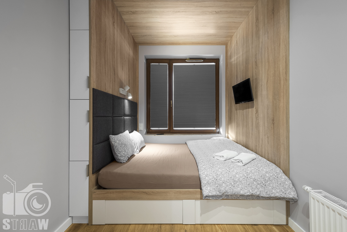 Sesje zdjęciowe apartamentów na wynajem, fotograf wnętrz Warszawa, sypialnia, łóżko podwójne, telewizor, okno, zagłówki, lampki nocne.