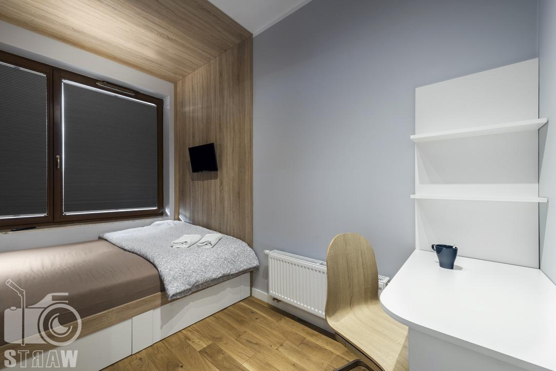 Sesje zdjęciowe apartamentów na wynajem, fotograf wnętrz Warszawa, sypialnia, gabinet, łóżko pojedyncze, stolik, krzesło półki, kaloryfer, okna.
