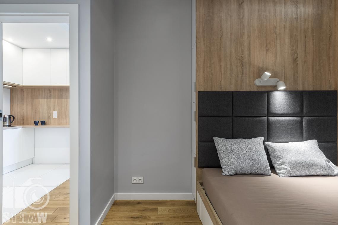 Sesje zdjęciowe apartamentów na wynajem, fotograf wnętrz Warszawa, sypialnia, łóżko podwójne, lampki nocne małe, widać kuchnię.
